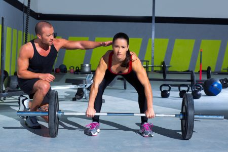 gym personal trainer man with weight lifting bar woman workout in exercise